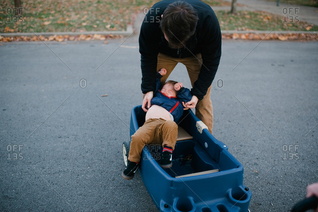 Father trying to put toddler into a wagon