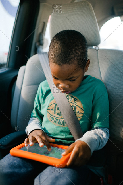 Boy playing on a tablet while riding in a car