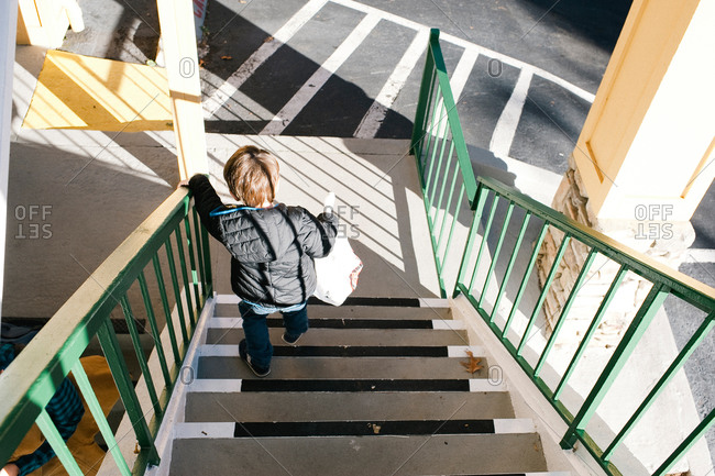 Boy carrying bag down outdoor stairs