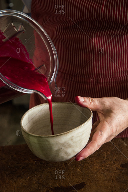 Pouring beet soup into pottery bowl
