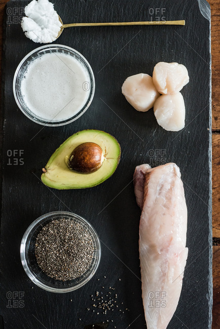Overhead view of monkfish, sea scallops, chia seeds and avocado on slate