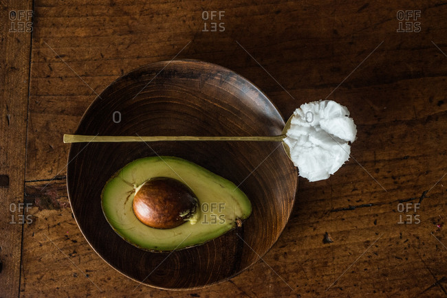 Avocado in bowl and spoonful of coconut oil