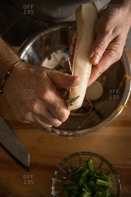 Chef peeling root with paring knife