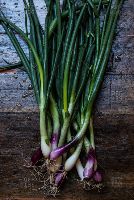 Fresh scallions with purple ends on wooden background