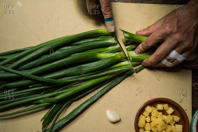 Chef with bandaged and taped fingers cutting scallions