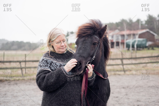 Older woman petting a horse's snout