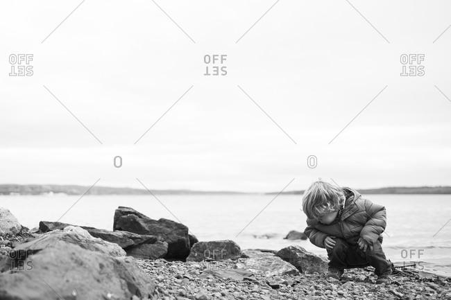 Toddler boy inspecting rocks at a seashore