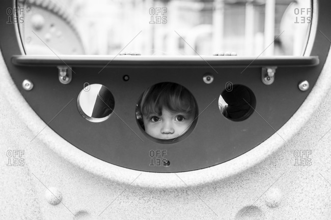 Toddler boy peaking throw a hole in playground equipment