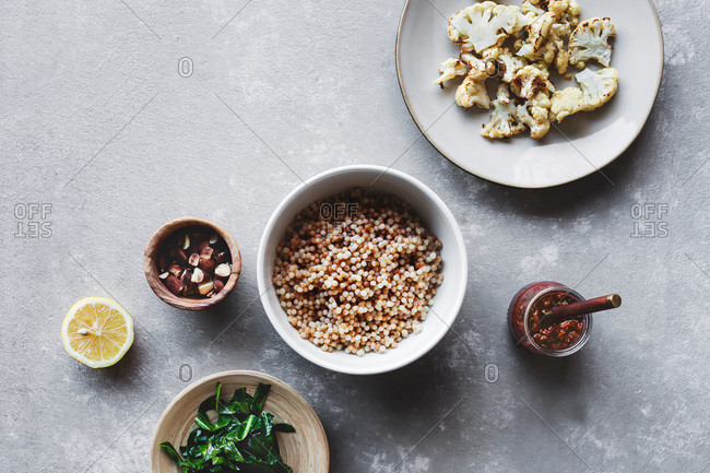Ingredients for Israeli couscous salad in a bowl and plates on a table