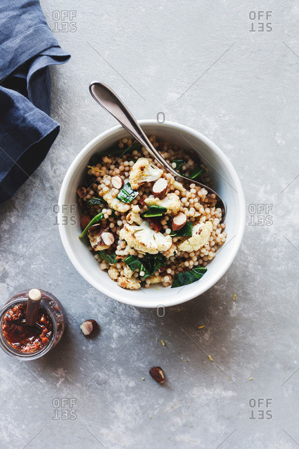 Prepared Israeli couscous salad with a side of sundried tomato pesto