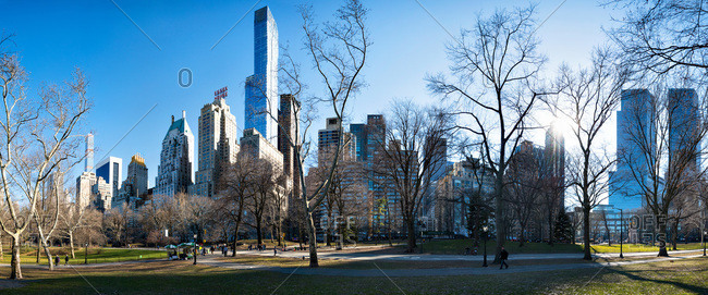 New York, NY, USA - April 1, 2015: Panorama of city skyline and park with the sun shining behind bare trees