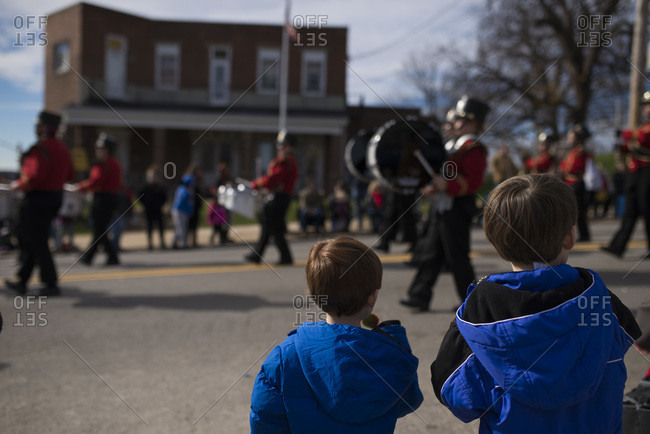 Boys watching a marching band in a parade