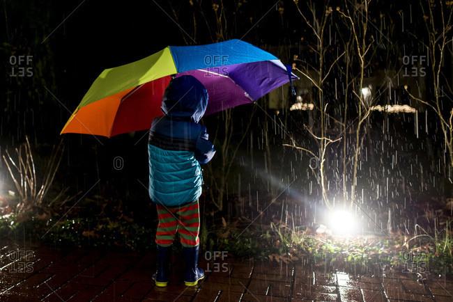 Boy with rainbow umbrella at night in rain