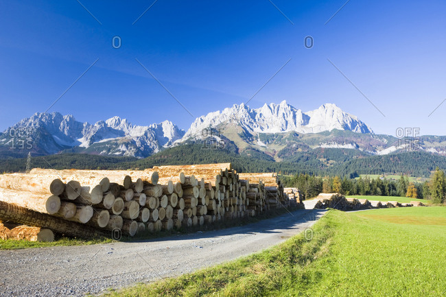 Logs on roadside, mountains in background, Austria