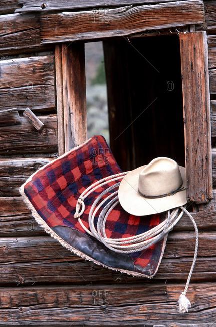 Cowboy gear in a cabin window