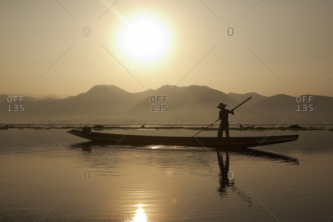 Silhouette of Burmese man on boat