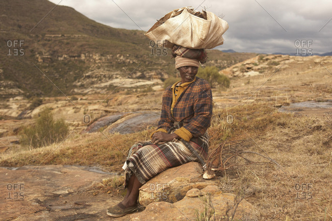 Lesotho - June 2011: Lesotho woman with firewood on head