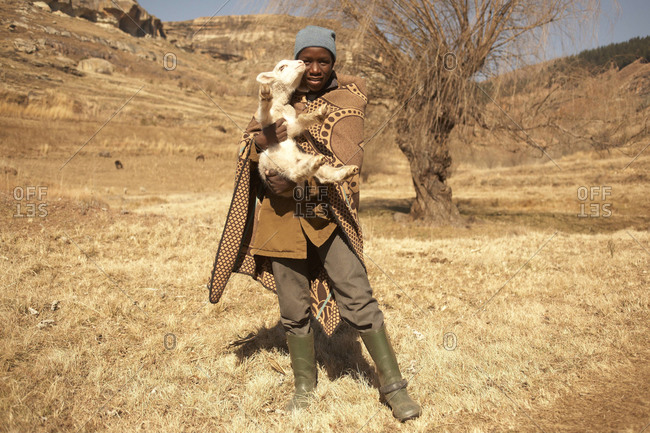 Lesotho - June 2011: Young boy in Lesotho holding a sheep