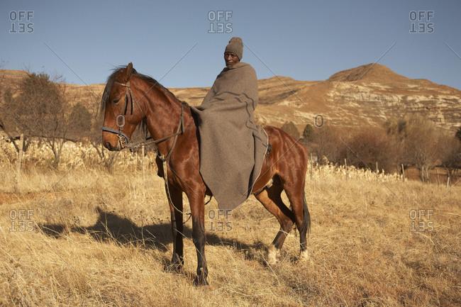 Lesotho - June 2011: Lesotho man in a blanket on horse