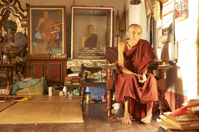 Burma - May 2011: Old monk staring off in a chair