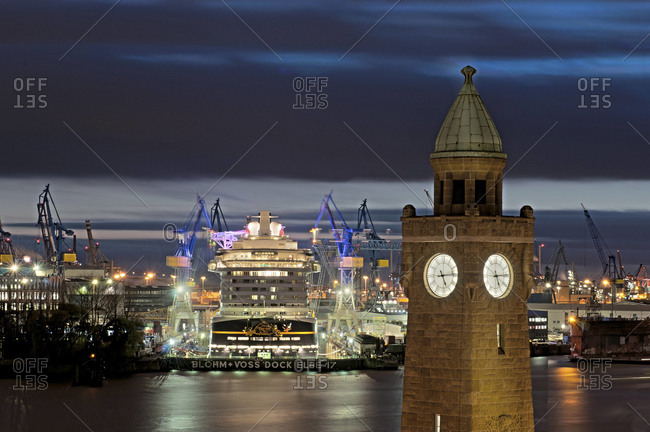Hamburg, Germany - February 11, 2011: Clock tower with seaport in background