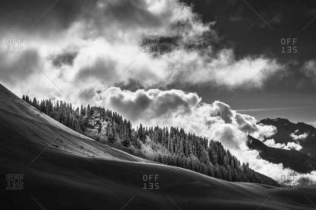 Clouds covering snowy mountain landscape