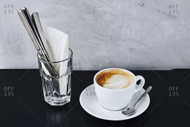 A cup of cappuccino with foam on Cafe table