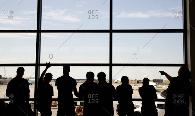 Travelers waiting at the window of an airport terminal