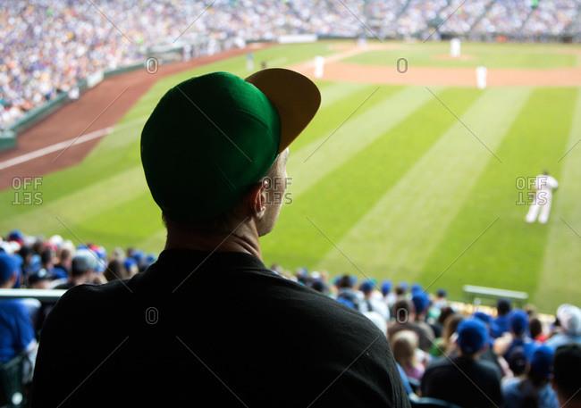 Man watching a baseball game at a stadium