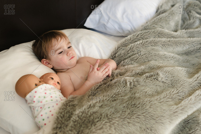 Little girl lying in bed under a furry blanket with her dolls