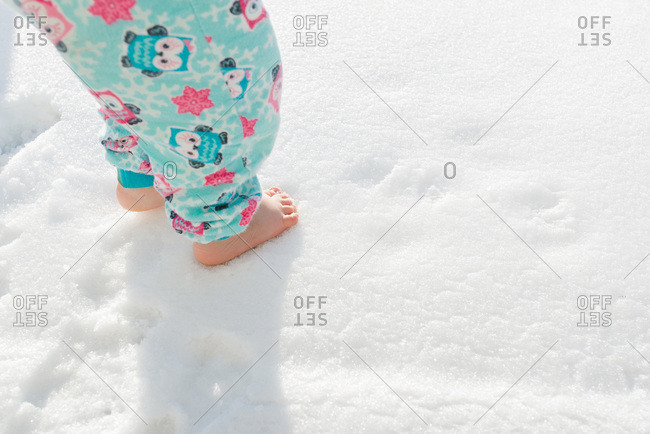 Bare feet of a little girl wearing pajamas in the snow