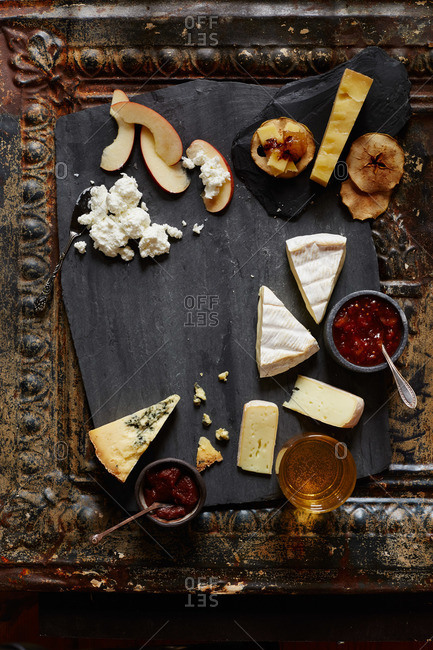 Variety of cheeses and fruit on a slate platter