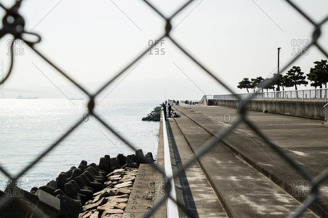View of fishermen on concrete embankment in Kobe Japan
