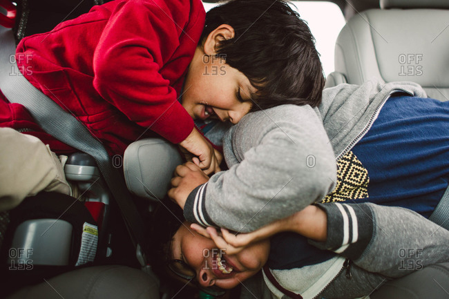 Rambunctious young brothers playing in their car seats