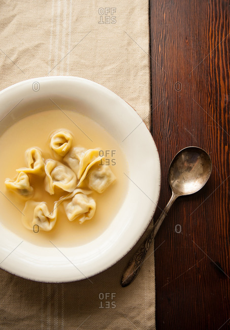 Overhead view of bowl of tortellini in broth