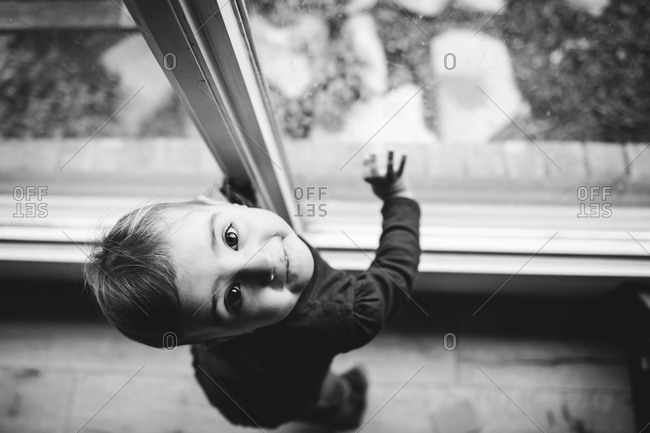 Little child standing by a window and looking up