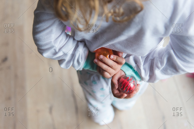 Little girl holding toys behind her back