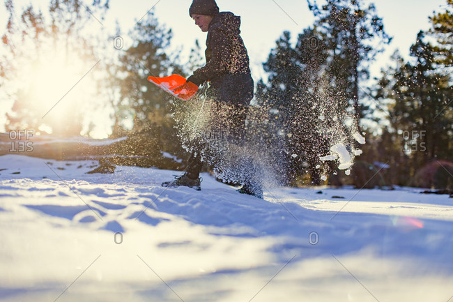 Woman shoveling snow in late afternoon sunlight