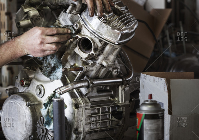 Motorcycle mechanic cleaning an engine
