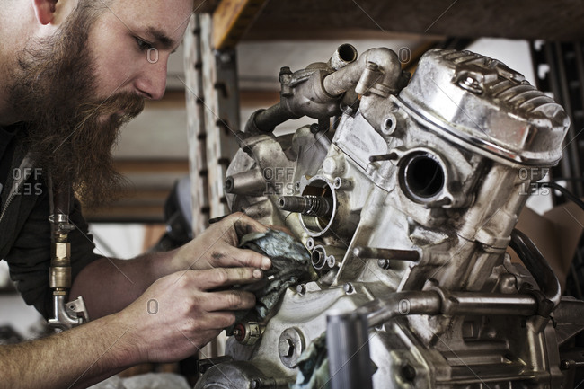 Motorcycle mechanic working on an engine