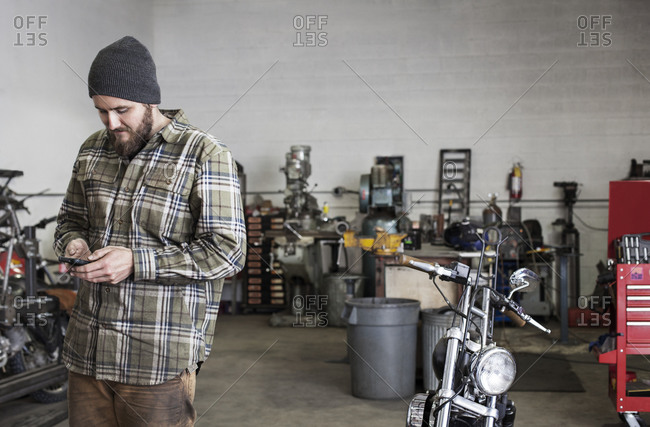 Motorcycle mechanic in a shop with a smartphone