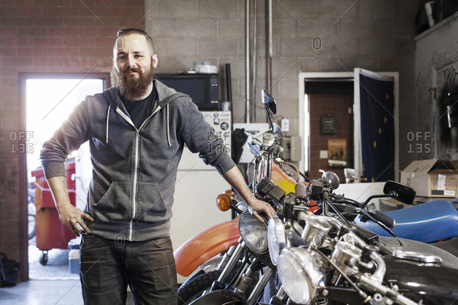 Portrait of a mechanic in a garage with motorcycles