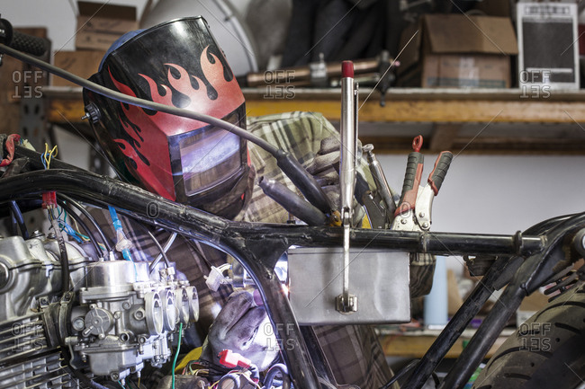 Mechanic welding parts onto a motorcycle