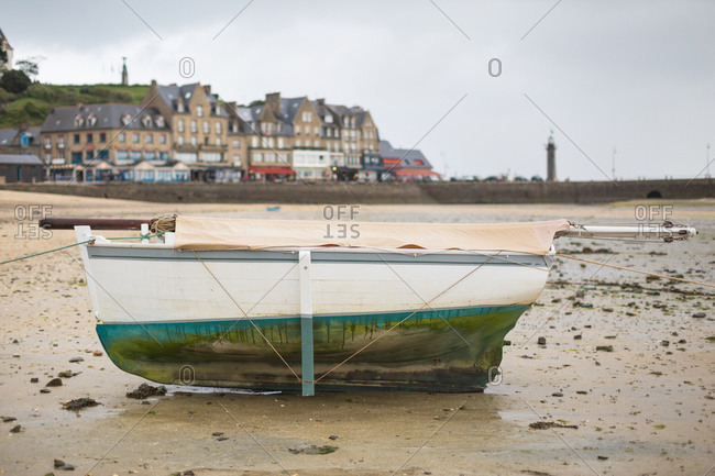 Small sailboat aground at low tide, Cancale, France