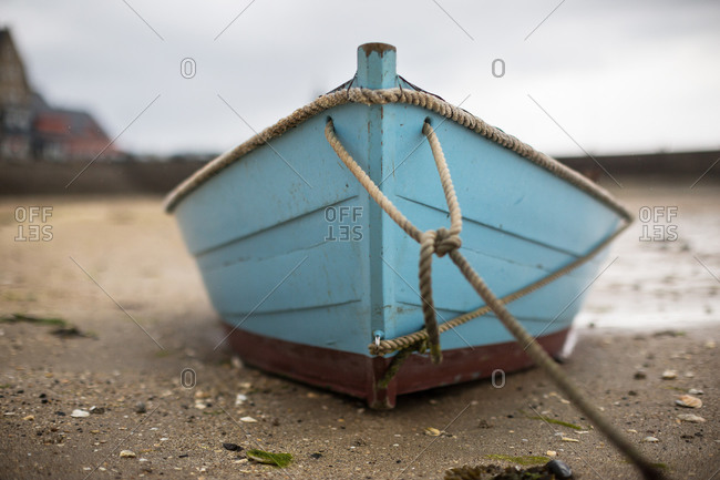 Small blue dory aground on beach at low tide, Cancale, France