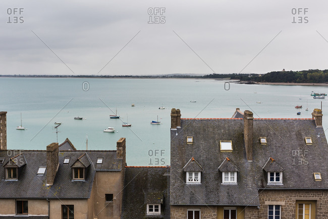 Houses and boats moored in harbor on cloudy day, Cancale, France