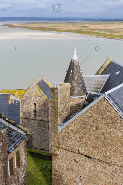 View of water and mainland through stone houses, Mont Saint-Michel, France