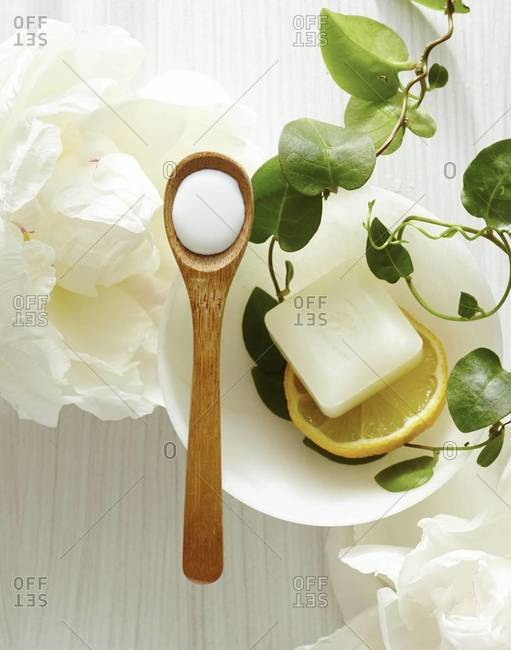 Overhead view of dish of lemon soap and white peony wooden spoon of cream at spa