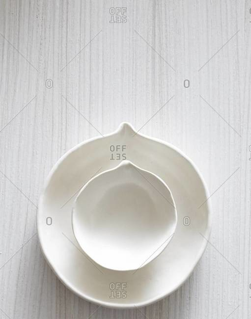 Overhead view of white ceramic dishes with spout on white wooden background