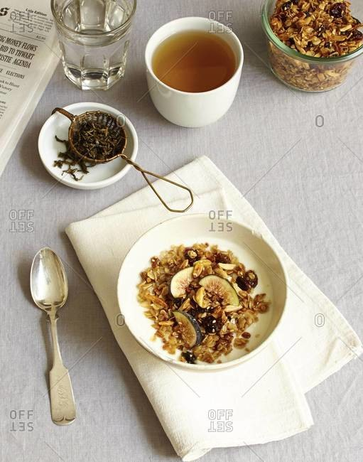 Elevated view of breakfast of tea, and granola in milk with tea